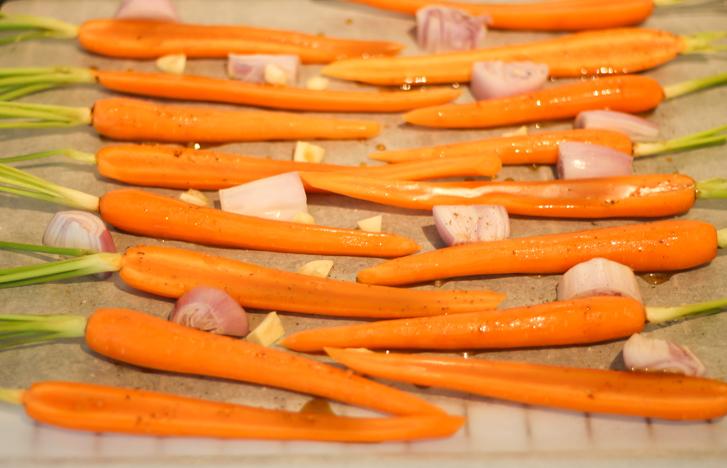Verdeel de worteltjes, sjalotten en knoflook gelijkmatig over het rooster